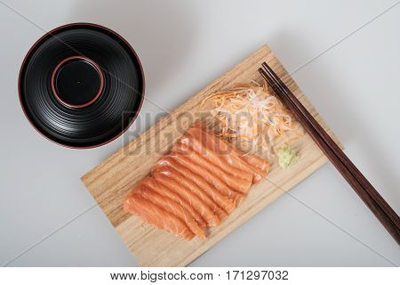 Top View Raw Salmon Sashimi On Wood Board, Chopsticks, And Soup
