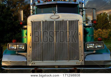 Front view of old green turquoise diesel Oregon logging truck with dramatic lighting