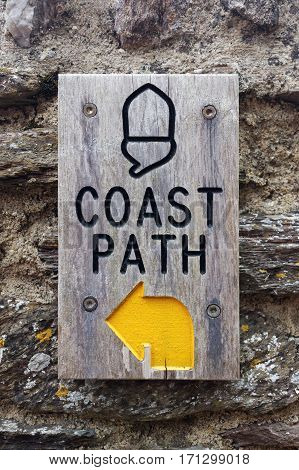 Stoke Fleming, Devon, UK, June 1, 2016. Editorial photograph of wooden route sign on the South West Coast Path in Stoke Fleming, Devon. The South West Coast Path National Trail follows 630 miles of coastline around Devon and Cornwall (vertical portrait fo