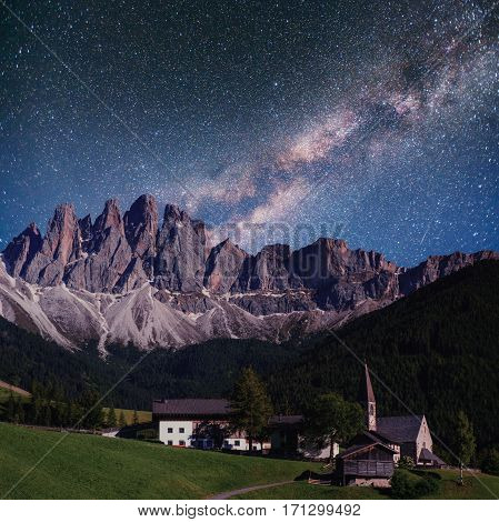 Starry sky above beautiful city in the mountains.
