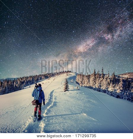 starry sky at night in the winter snow. Milky Way is a fantastic New Year's Eve. Tourists on winter road in the mountains
