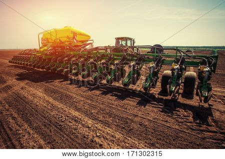 Tractor plowing farm field in preparation for spring planting.