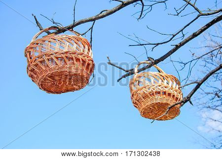 Trade of Handicrafts in the street in the spring. Wicker baskets hung on the branches of trees on the background of blue sky