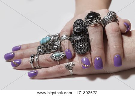 Various silver rock rings with nice manicured fingernails. Soft focus poster