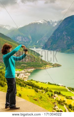 Tourism and travel. Woman tourist taking photo with camera enjoying mountains fjords view in Sogn og Fjordane county. Norway Scandinavia.