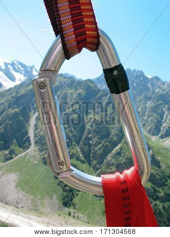 Climbing carabiner closup on the mountains background.