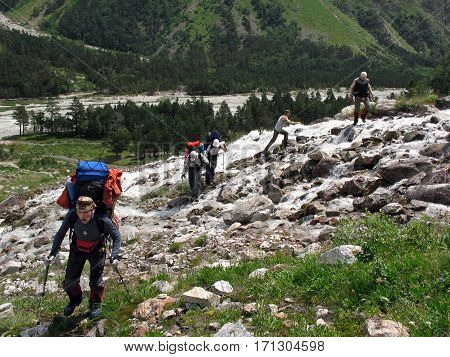 CAUCASUS/ RUSSIA - AUGUST 2, 2007: The climbers are crossing a flashy mountain river in the gorge Adyr-Su. Caucasus, Russia.