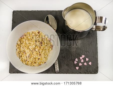 nutritious breakfast of oatmeal with fruit and milk on a black stone plate and purple hearts morning meal