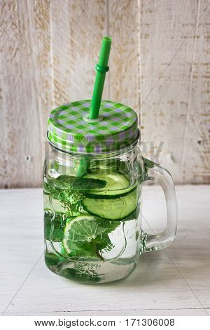 Mason jar mug with handle, lid and straw with detox cucumber agua fresca water with lime and mint ingredients, on rustic wood kitchen table, spring cleansing