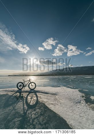 Fatbike also called fat bike or fat-tire bike - Cycling on large tire wheels. Cyclist goes to his bike on the frozen lake. Picture taken in HDR mode.