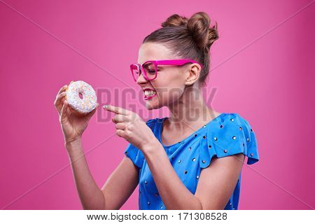 Side view of an angry woman pointing at the doughnut over pink background. Young girl in pink glasses clenched teeth