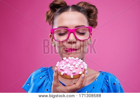 Extreme close-up of stylish woman enjoying a delicious donut. Woman licking the sugar off her lips