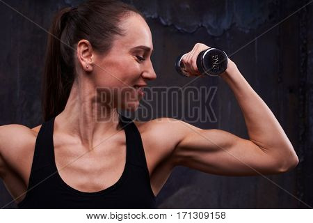 Extreme close-up of perfectly trained biceps of woman arm isolated over black background. The concept of sports and fitness. Strong and powerful young woman doing exercise with dumbbells