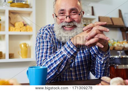 Close-up of pleased Caucasian male sits with elbows on table looking at the camera. A cup of tea standing on the table. Leaning elbows on table, hands clasped