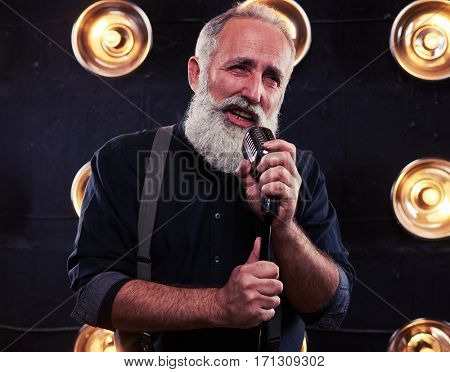 Close-up of passionate performer singing with a microphone in a studio lighting. Using the classical vintage standing microphone