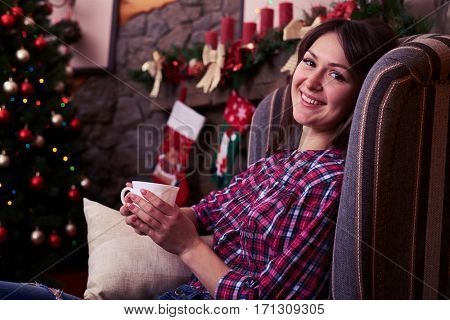 Close-up of overjoyed youth relaxing in an armchair against decorated fireplace. Nice Christmas tree near the fireplace. Festive illumination. Christmas scene with tree in background