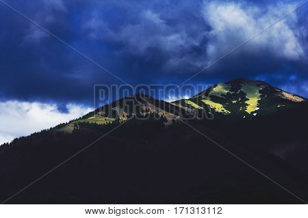 Dark clouds hung over the top of the mountain, which illuminated by sunlight. Landscape with contrasts