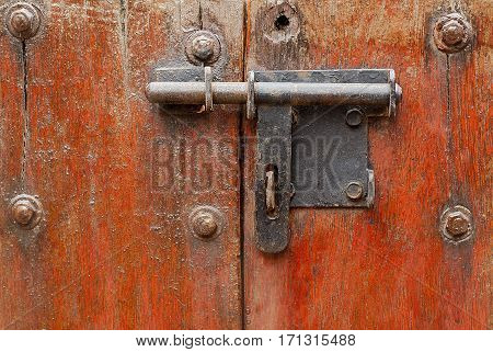 Vintage stylized old metal hasp on old vintage wooden door