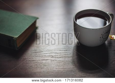 Book and brewing cup of tea on wooden table