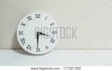 Closeup white clock for decorate show half past three p.m. or 3:30 p.m. on white wood desk and cream wallpaper textured background with copy space