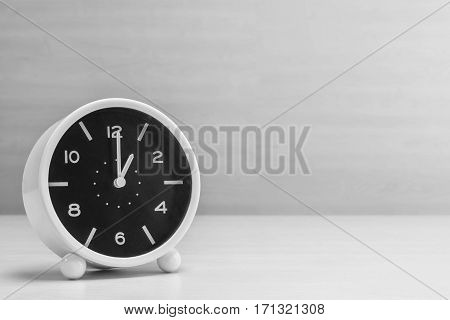 Closeup alarm clock for decorate in 1 o'clock on wood desk and wall textured background in black and white tone with copy space