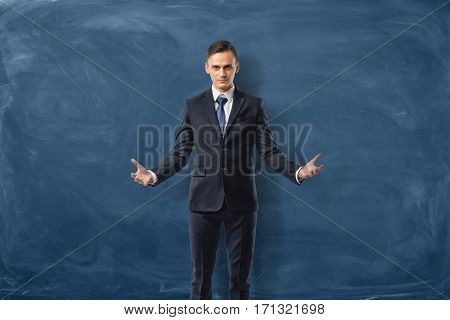Successful businessman is standing with open arms isolated on blue chalkboard background. Leader's qualities. Success in business. Inner strength