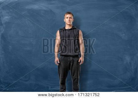 Muscular young man is standing on the blue chalkboard background. Sport and healthy lifestyle. Keeping fit. Athletic body
