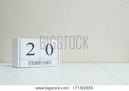 Closeup white wooden calendar with black 20 february word on blurred white wood desk and cream color wallpaper in room textured background with copy space in selective focus at the calendar