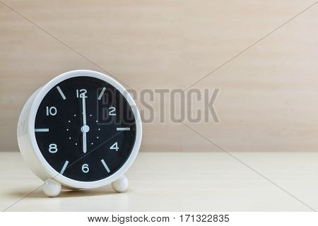 Closeup alarm clock for decorate in 6 o'clock on brown wood desk and wall textured background with copy space