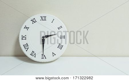 Closeup white clock for decorate show half past two p.m. or 2:30 p.m. on white wood desk and cream wallpaper textured background with copy space