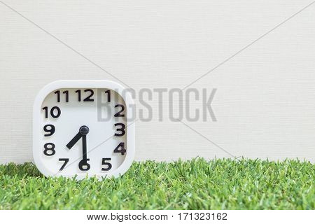 Closeup white clock for decorate show a half past seven or 7:30 a.m. on green artificial grass floor and cream wallpaper textured background with copy space