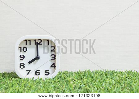 Closeup white clock for decorate in 8 o'clock on green artificial grass floor and cream wallpaper textured background with copy space