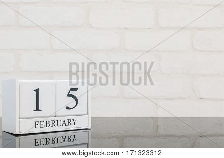 Closeup white wooden calendar with black 15 february word on black glass table and white brick wall textured background with copy space in selective focus at the calendar