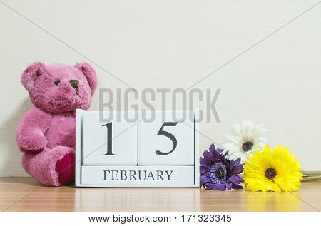 Closeup surface white wooden calendar with black 15 february word on brown wood desk and cream color wallpaper in room textured background with copy space in selective focus at the calendar