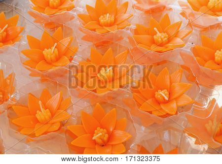 Small carved orange lotus flower shape candles for make merit in Buddhist Thai temple