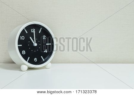 Closeup black and white alarm clock for decorate in 11 o'clock on white wood desk and cream wallpaper textured background with copy space
