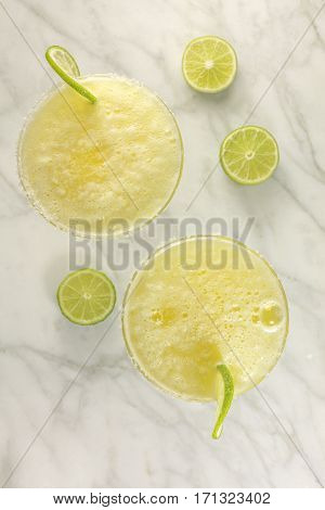 An overhead shot of two lemon Margarita cocktails with wedges of lime on a white marble table with copy space