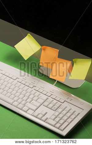 Computer screen and keyboard with colored paper attached to the monitor.