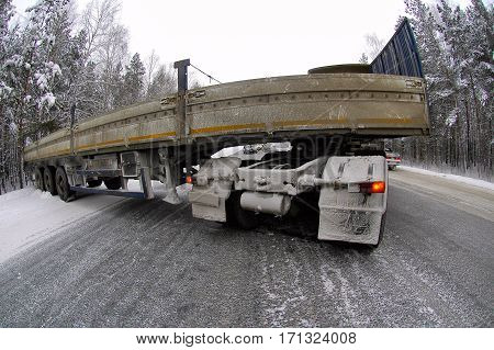 Drift of the long truck on the winter road because of braking