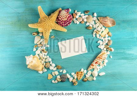 An overhead photo of a sea star, sea shells, and pebbles forming a frame on a vibrant turquoise background, with a business card inside. A design template for a summer vacation banner