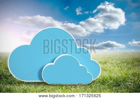 Digitally generated image of blue cloud shapes against sunny landscape 3d