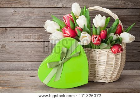 Colorful tulips bouquet and gift box in front of wooden wall. Red and white. With space for your greetings
