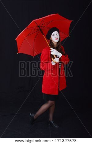 young brunette woman in a suit holding a mime standing under a red umbrella on a dark background