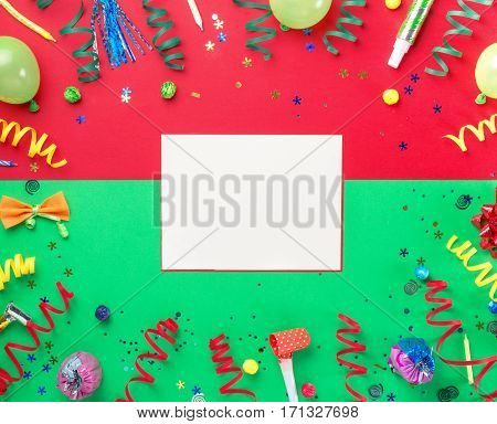 Blank card with colorful party items on a colorful background. Flat lay