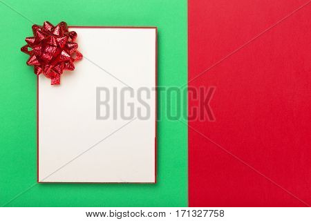 Blank card with a red bow on a colorful background top view. Colorful celebration background