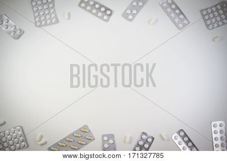 Different medical tablets, capsules and pills in blister pack frame as background with copy space for text or image