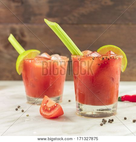 A square photo of Bloody Mary cocktails with slices of lime, celery sticks, a piece of tomato and copyspace