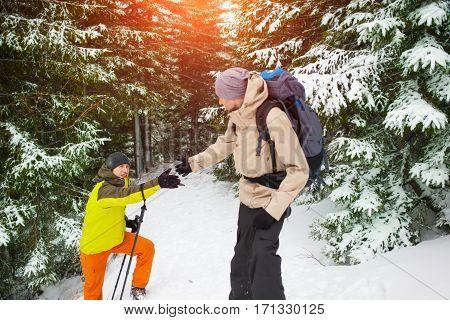 Man Helping Friend To Climb.