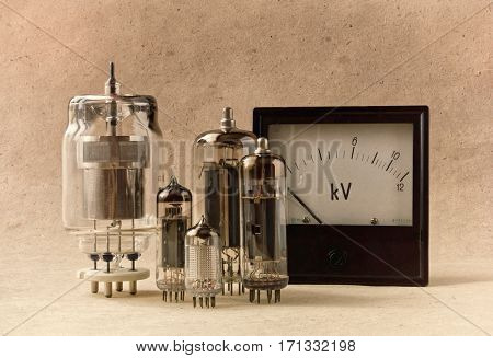 vintage electronic background with vacuum tubes and voltmeter on kraft paper