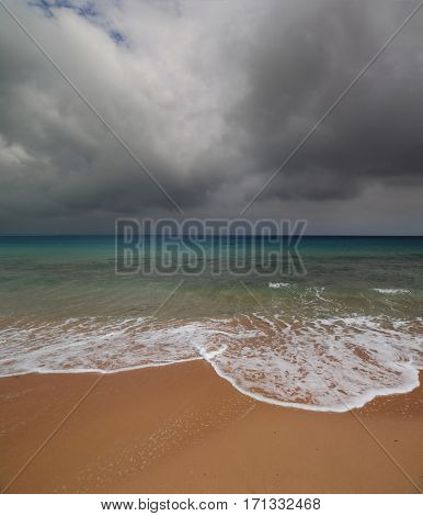 dramatic sand beach sea landscape with moody sky